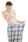 Successful losing weight, woman in big trousers. White background Stock Photos