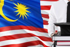 Successful Malaysian student education concept. Holding books and graduation cap over Malaysia flag background royalty free illustration