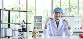 A successful male chemist is examining his new innovation in a laboratory. This breakthrough substance is to be used in medical industry stock image