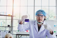 A successful male chemist is examining his new innovation in a laboratory. This breakthrough substance is to be used in medical industry stock photos