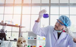 A successful male chemist is examining his new innovation in a laboratory. This breakthrough substance is to be used in medical industry stock images