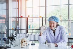 A successful male chemist is examining his new innovation in a laboratory. stock photography