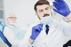 Successful male dentist fixing light stock photo