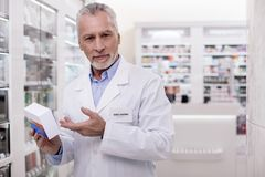 Successful male pharmacist taking new medication. Experienced pharmacist. Senior appealing male pharmacist gazing at camera while carrying medication Stock Photography