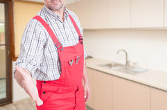 Successful male plumber doing welcoming gesture. Successful male plumber doing welcoming or handshake gesture inside in the kitchen Stock Photo