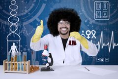 Successful male scientist showing thumbs up. Portrait of successful male scientist showing thumbs up and chemical fluid at working on scientific research. Shot Stock Photo