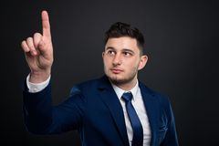 Successful male in suit pointing on empty screen. As modern technology concept Stock Image
