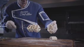 Successful man in blue chef uniform cooking lula kebab in modern turkish restaurant. Cook stringing kebab pieces wrapped. Skillful man in blue chef uniform stock video footage