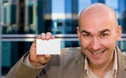 Successful man with business card. Smiling successful man showing his business card Royalty Free Stock Photo