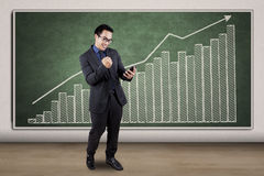 Successful man with cellphone and graph Royalty Free Stock Photo