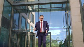 Successful man is dancing near the modern building