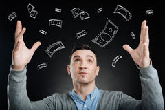 Successful man enjoying money rain. Earn as much as you can. Concentrated rich man enjoyign money rain and holding his hands up in the air royalty free stock photo