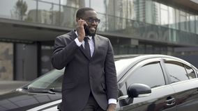 Successful man in expensive suit communicating on phone, standing near his car. Stock footage stock video