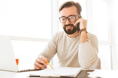 Successful man in eyeglasses running business from home workplac. E speaking on smartphone and writing down notes on paper Royalty Free Stock Images