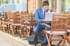 Successful man hands up outdoor at cafe. Successful man talking by mobile phone outdoor at French cafe, Paris. Using laptop. Concept of success deal. Online royalty free stock image