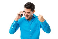 Successful Man Receiving Good News On Mobile Phone. Successful young man receiving good news on mobile phone over white background royalty free stock photos