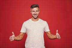 Successful man 30s in striped t-shirt gesturing and demonstratin royalty free stock photos