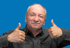 Successful man shows ok sigh. On a blue background Stock Image