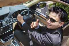 Successful man shows thumb up in new car Stock Photos