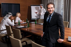Successful man sitting on the table. Feel the progress. Positive delighted bearded men leaning against the table wand conducting the conference while two Arabic Royalty Free Stock Images