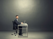 Successful man smiling in the dark room Royalty Free Stock Images