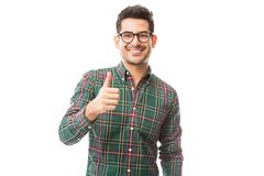 Successful Man Smiling While Gesturing Thumbs Up. Successful young man smiling while gesturing thumbs up on white background royalty free stock images