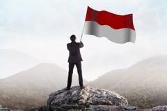 Successful man waving Indonesian flag Stock Photo