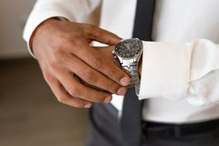 Successful man with white shirt and necktie looks on watch royalty free stock image