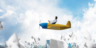 Successful management and information analysing. Concept with funny pilot. Aviator driving propeller plane above falling paper sheets with diagrams. Young man royalty free stock photos
