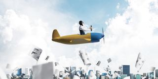 Successful management and information analysing. Concept with funny pilot. Aviator driving propeller plane above falling paper sheets with diagrams. Young man royalty free stock photo