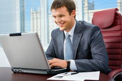 Successful manager. Typing on the laptop in his office royalty free stock photo