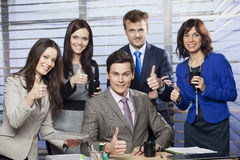 Successful manager sitting at the desk. Surrounded by his business team Stock Photos