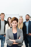 Successful manageress or team leader. Standing in front of her colleagues with folded arms smiling at the camera Stock Photography