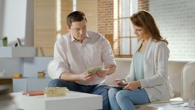 Successful married couple counting cash at home, family budget money, savings. HD stock photo