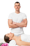 Successful massage therapist and a girl on a massage table Stock Images