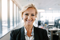 Successful mature businesswoman standing in office stock images