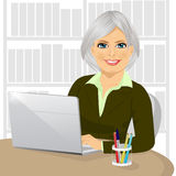 Successful mature businesswoman working typing on her laptop at office. Portrait of successful mature businesswoman working typing on her laptop at office Stock Photo