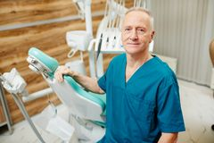 Senior dentist. Successful mature dentist standing by his workplace in dental clinics Royalty Free Stock Images