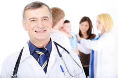 Successful mature doctor and the young family Royalty Free Stock Photo
