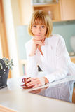 Successful mid aged woman with a cup of coffee Royalty Free Stock Photography