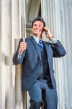 Successful Middle Age American Businessman talking on cell phone. Dressing in dark blue three piece suit, necktie, a handsome, sexy, middle age businessman is Stock Photos
