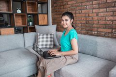 Casual woman with laptop. Successful middle aged woman smiling while playing her laptop Royalty Free Stock Image