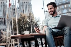 Successful millennial guy smiling while working outdoors Royalty Free Stock Photography