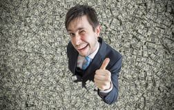Successful millionaire covered with money is showing thumbs up gesture.  Royalty Free Stock Photo