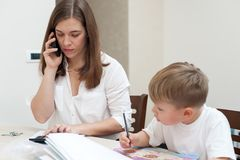 Successful mother works at home with her son stock photography