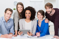 Successful motivated multiethnic business team. Posing grouped around an attractive African American women looking at the camera with beaming friendly smiles Stock Image
