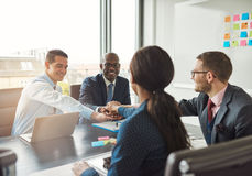 Successful multiracial business team. Working together affirm their commitment by linking hands across an office table during a meeting stock images
