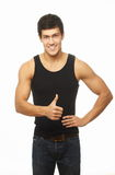 Successful muscled young man showing thumb up Stock Images