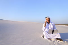Successful Muslim male architect communicates on phone with clie Royalty Free Stock Photo