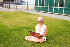Successful Muslim woman and laptop. Arab businesswoman wearing hijab working on a laptop in the park. Stock Images
